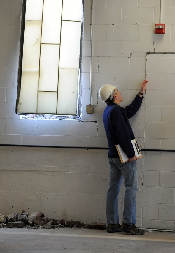 While demolishing the Old Town Canoe building on Brunswick Street, the structure crashed into the Old Town Fire Department wrecking the fire escape stairs, breaking two windows, and cracking the wall in several areas.  Jamie Mahoney, former engineer at Ames and engineer/designer of the fire department's previous renovations, checks a crack in the wall from the impact that happened at about 8:30 a.m. Thursday.