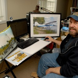 "Professional photographer Bob Hirshberg sits at a computer workstation inside his business, Scruffyy Productions, which is based in Glenburn. Among the photo-oriented products that he produces and sells are (from left) a steamship ""Katahdin"" image printed on a silk pillow, a 2014 Bangor calendar, and a matted and framed color photo of an Aeronca Champ seaplane on a ramp at the Lucky Landing Seaplane Base on Pushaw Lake in Glenburn."