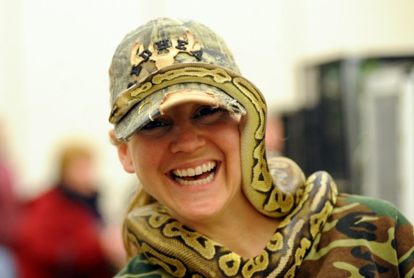 Kate Anderson of Concord, New Hampshire, laughs as Bruce, a ball python, slithers around her ball cap at the start of the Northeast Reptile Expo on Sunday at the Cross Insurance Center. Kate and her husband, Josh, own WTF Reptiles in New Hampshire.