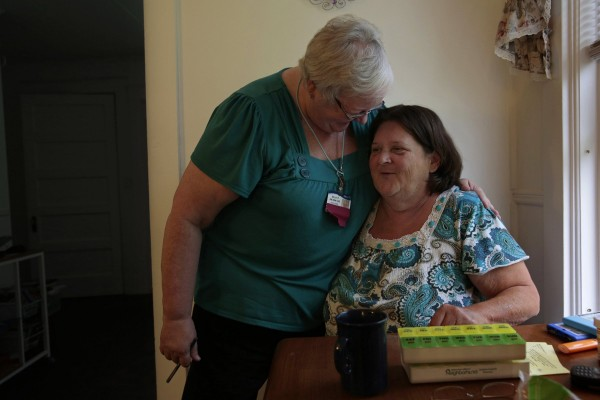 Sally Patterson, of Eastern Maine Homecare, left, checks in on patient Christine McDonald at her home in Carmel, Maine, Sept. 12, 2013.
