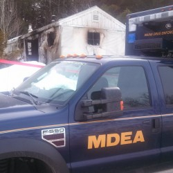A Maine Drug Enforcement Agency vehicle sits outside a mobile home in Danforth that caught fire Friday not long after a 5-month-old boy was reported dead at the home. Police charged the boy's parents with drug trafficking Saturday after investigators examining the fire scene found evidence of methamphetamine manufacturing inside the home.