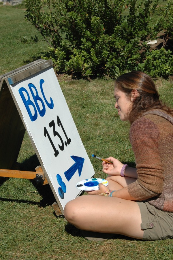Painting a directional sign in the sunshine at Blueberry Cove.