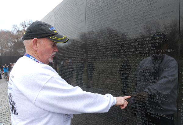 Fred Small, a Vietnam veteran from Vinalhaven, touches the name of a fallen friend etched into the Vietnam War memorial wall in Washington, D.C.