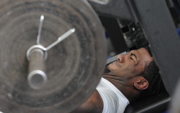 UMaine football player Derrick Johnson bench presses 225 pounds for NFL scouts during pro day at the University of Maine on Monday.