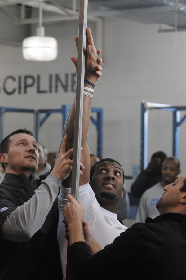 UMaine football player Derrick Johnson has the vertical jump test adjusted for his height by two NFL scouts during pro day at the University of Maine on Monday.