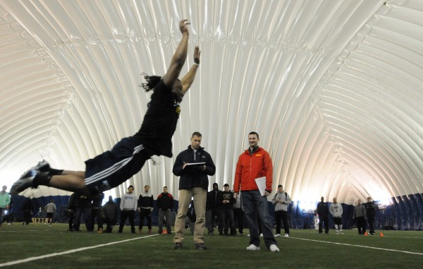 NFL scouts watch and record the results as UMaine football player Rickey Stevens tests on the broad jump during pro day at the University of Maine on Monday.