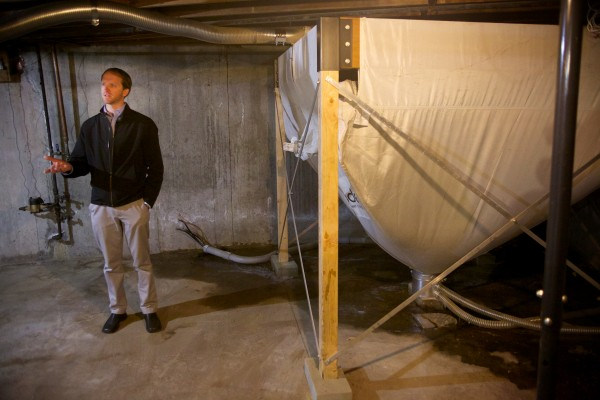 Ryan Hamilton of Interphase Energy in Portland stands in a basement by an air-driven wood pellet hopper which feeds a high-tech wood pellet boiler his company sells on Thursday.