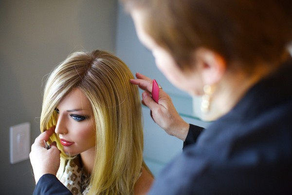 Charlene Boggins brushes a wig on one of her mannequins at her Salon in Veazie. Boggins owns Nourish Salon where she works with women going through cancer treatment and facing hair loss.