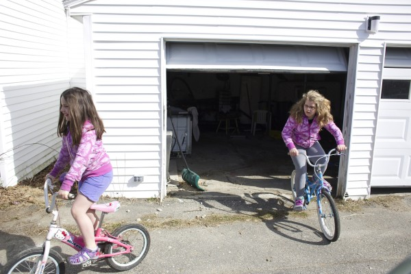 Zoe (from left), 8, and Lily Hadjaissa, 10, ride bikes out of their garage at their Richmond home.