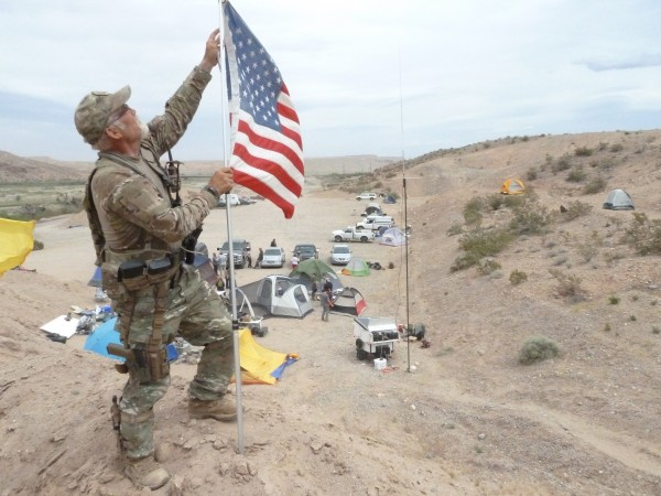 Jerry DeLemus, a 59-year-old self-employed construction worker from Rochester N.H., has been appointed the commander of a camp where armed supporters of Nevada rancher Cliven Bundy live and patrol his ranch and cattle. Here DeLemus fixes a U.S. flag that got tied up in the 50 mph winds on April 22, 2014.