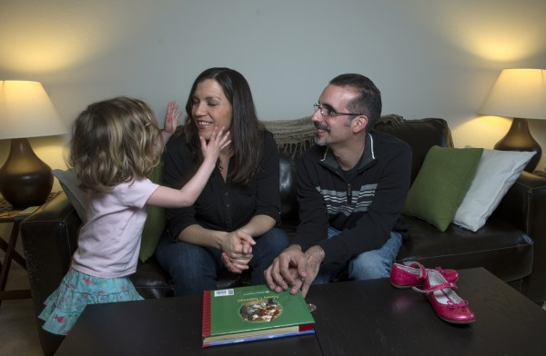 Susan and Dan Hartmann play with their daughter at home in Odenton, Md. Dan is HIV-positive, but Susan and the child are not.