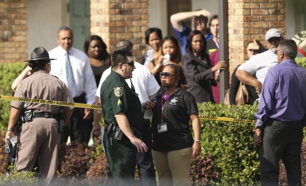 Parents wait behind as police consult after a child was killed and several were injured after being struck by a vehicle at a KinderCare Learning Center in Winter Park, Florida April 9, 2014.
