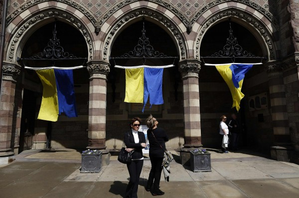 Pedestrians look at a marathon banner installation at the Old South Church on Boylston Street in Boston, Massachusetts, April 14, 2014. Tuesday marks the one-year anniversary of the Boston Marathon bombing on April 15, 2013.
