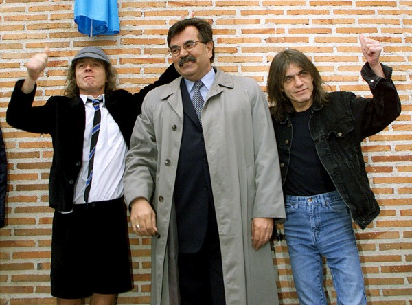 Angus (L) and Malcolm (R) Young, founder members of Australian heavy metal band AC/DC, flank Jose Luis Perez, mayor of the Madrid district of Leganes, following the inauguration of a new street with the group's name in this file photo taken March 22, 2000.