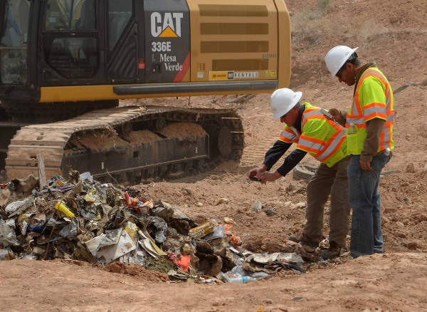 Workers take photos of recovered Atari games at the old Alamogordo landfill in Alamogordo, New Mexico, April 26, 2014.