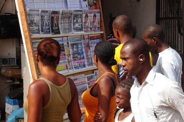 People read news headlines at a newsstand in Conakry March 28, 2014.