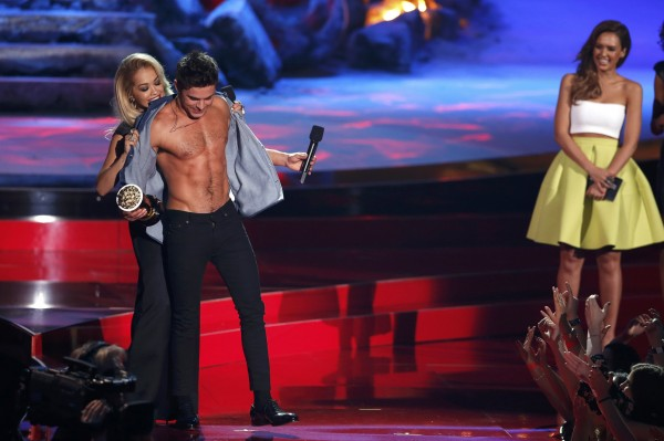 Zac Efron accepts the award for best shirtless performance for &quotThat Awkward Moment&quot as his shirt is ripped open by presenter Rita Ora at the 2014 MTV Movie Awards in Los Angeles, California.