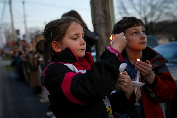 Ashlin (L) and Jude Burkhart, from Murrysville, hold candles during a prayer vigil for victims of the Franklin Regional High School stabbing rampage, at Calvary Lutheran Church in Murrysville, Pennsylvania April 9, 2014.