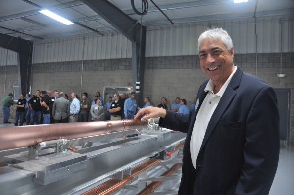 Peter Anania, owner of Mega Industries, shows off a piece of equipment designed by a summer intern from the University of Maine that his company uses in the manufacturing of microwave transmission equipment.