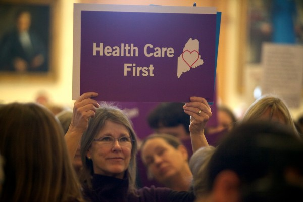 A woman holds a sign at a rally and lobby day organized by the Maine Peoples Alliance at the State House in Augusta on Jan. 8 around the issue of Medicaid expansion.
