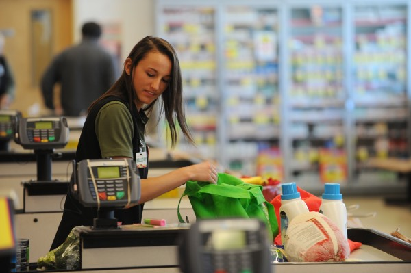 Husson softball player Mallory Conary bags groceries for a customer at Shaws on Main street in Bangor on Wednesday.