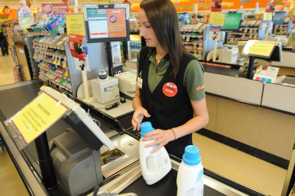 Husson softball player Mallory Conary rings up groceries for a customer at Shaws on Main street in Bangor on Wednesday.