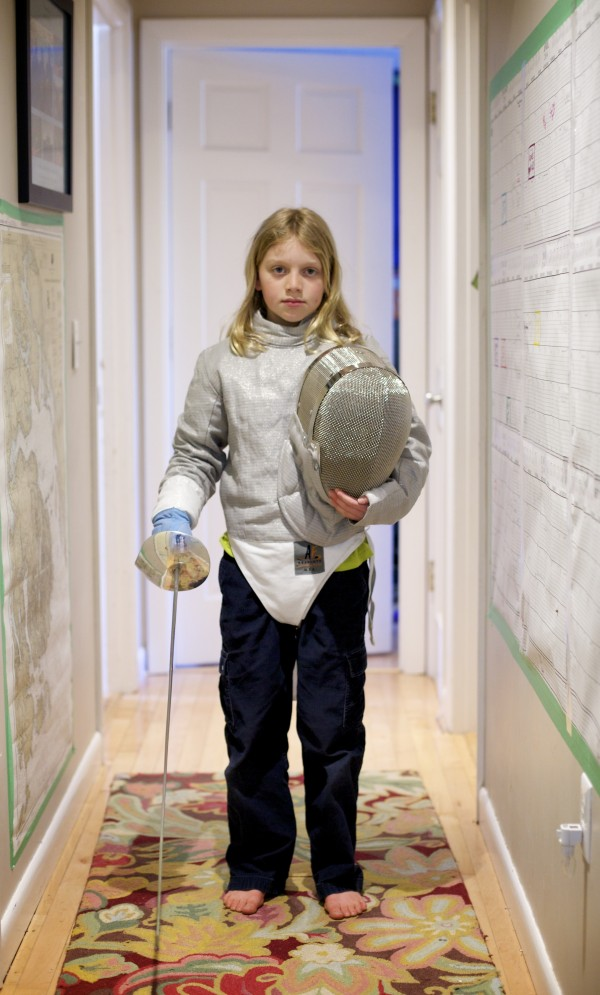 Erin Gerbi, 11, shows off part of her fencing uniform at her home in Orono on Tuesday.