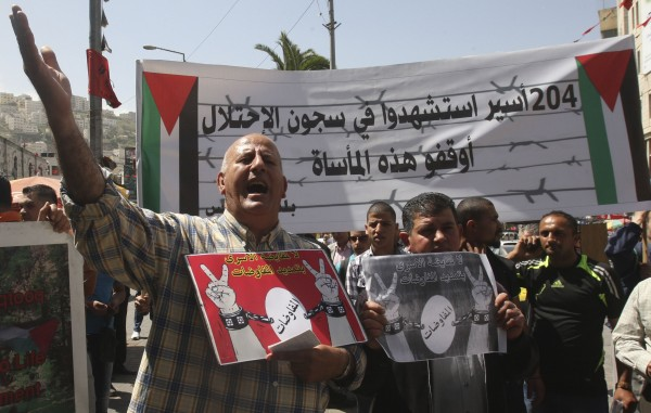 A Palestinian man shouts slogans during a protest calling for the release of Palestinian prisoners held in Israeli jails, in the West Bank city of Nablus April 7, 2014.
