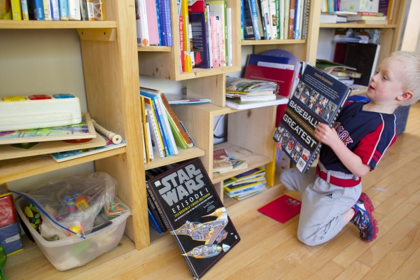 Evan Gerbi, 5, shows off some of his baseball books that his mother Aimee uses has part of his home-school curriculum in Orono on Tuesday.