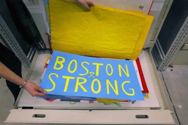 Archivist Marta Crilly holds a poster, an artifact saved from the makeshift Boston Marathon bombing memorial, at the City Archives in Boston, Massachusetts March 27, 2014.