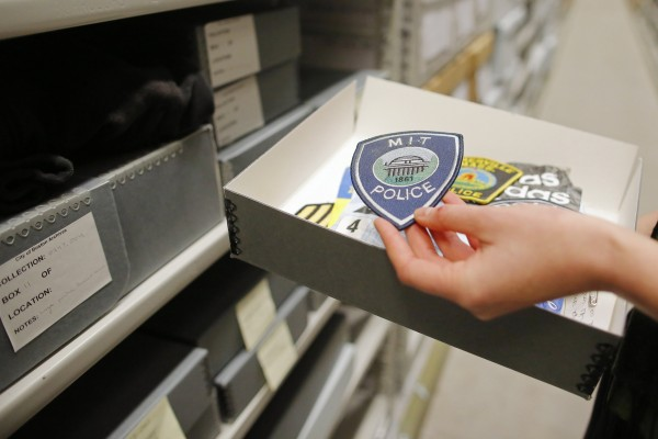 Archivist Marta Crilly holds a patch from the M.I.T. police force, an artifact saved from the makeshift Boston Marathon bombing memorial, at the City Archives in Boston, Massachusetts March 27, 2014.