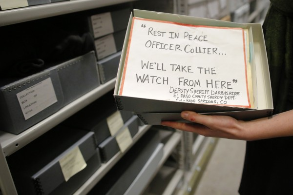 Archivist Marta Crilly holds a sign which reads, &quotRest in Peace Office Collier...We'll Take the Watch from Here&quot, an artifact saved from the makeshift Boston Marathon bombing memorial, at the City Archives in Boston, Massachusetts March 27, 2014.