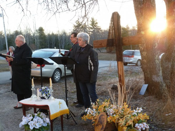 The sun appears between tree trunks outside the East Bucksport United Methodist Church on Easter morning as the Rev. Peter Remick reads from the Gospel about the discovery of Christ's empty tomb.