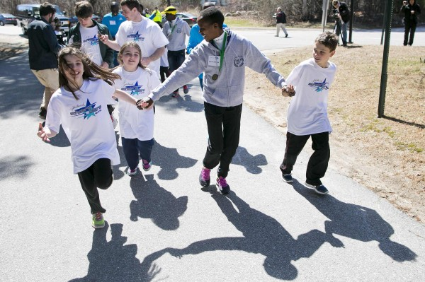 Marathoner Jemima Sumgong takes a friendly lap around school grounds as elite runners from the Kenyan team meet students at Elmwood Elementary School in Hopkinton, Mass., April 17, 2014.