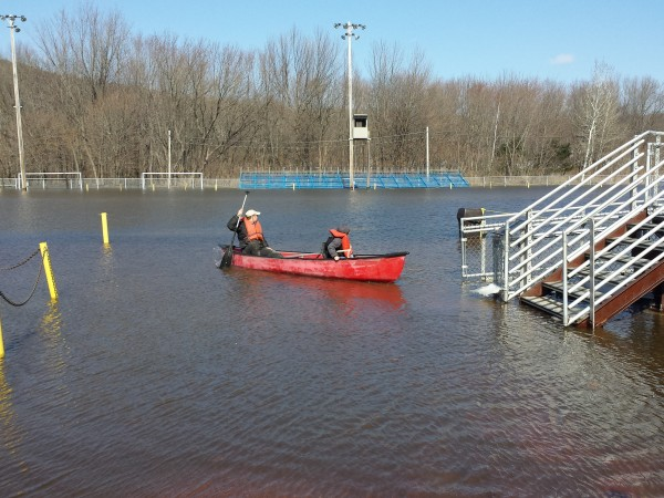 An unidentified couple canoes Wednesday near the bleachers of Hosmer Field in Rumford, which normally serves as the Mountain Valley Falcons football field and track. The Androscoggin River, although it appears to be receding, swelled over its banks this week.