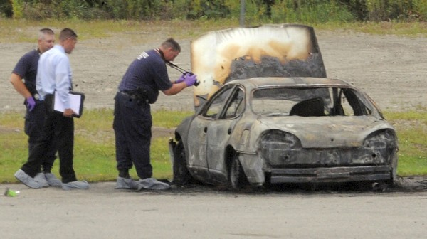 Police investigate a vehicle that burned before dawn Monday, Aug. 13, 2012, off Target Industrial Circle in Bangor, Maine.  After the fire was extinguished, three bodies were found inside the parked car.