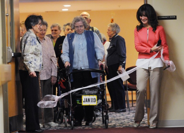 Susan McDonald (left), assistant to Ellen M. Leach Memorial Home executive director Corenna O'Brien (right), drops the ribbon for residents including Janet Barker (center) for the start of the second annual Easter Egg Hunt at the retirement home in Brewer on Tuesday.
