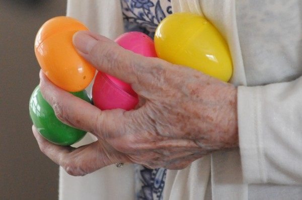 A resident at the Ellen M. Leach Memorial Home holds a handful of plastic Easter eggs during the second annual Easter Egg Hunt at the retirement home in Brewer on Tuesday.