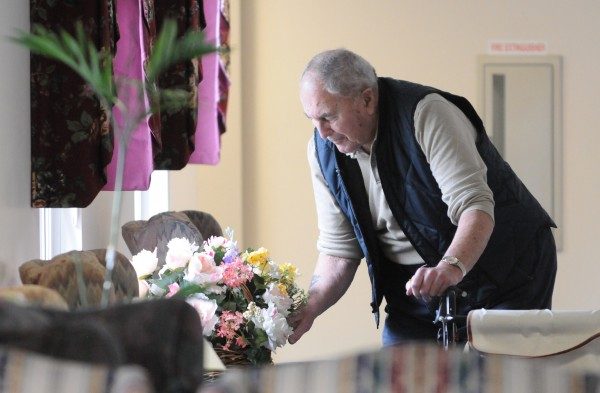 Bud Flosom, a resident at the Ellen M. Leach Memorial Home, searches a flower arrangement looking for plastic Easter eggs during the second annual Easter Egg Hunt at the retirement home in Brewer on Tuesday. 160 eggs were hidden around the three-story building, 120 containing prize numbers to be redeemed next Monday.