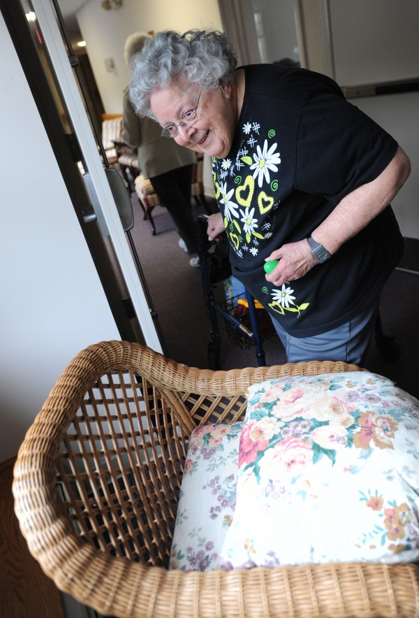 Lorraine Evans, a resident at the Ellen M. Leach Memorial Home, grabs a plastic Easter egg from behind a chair cushion during the second annual Easter Egg Hunt at the retirement home in Brewer on Tuesday.