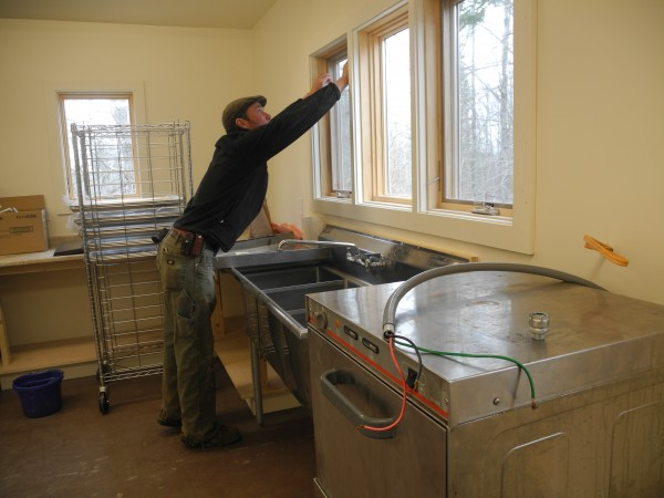 Phil Retberg, the steward of Halcyon Grange, works Saturday on the grange's kitchen expansion and renovation project. The grange, which was chartered in 1898, is looking toward the future with many new members and a plan to create a community kitchen, where local farmers can add value to their crops.