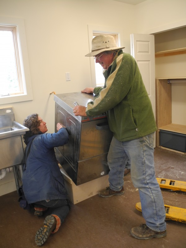 Halcyon Grange members Heather Retberg (left) and Doug Wollmar work to install a new sterilizing dishwasher Saturday in the just-renovated grange kitchen.