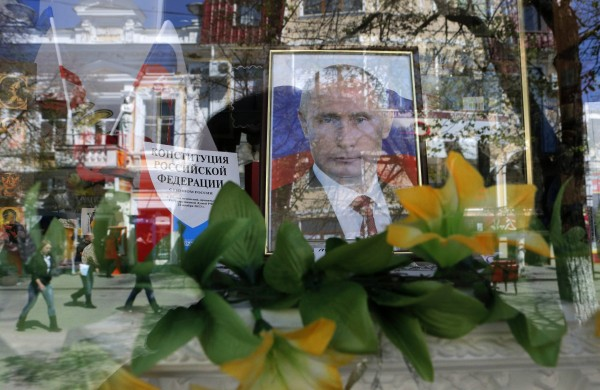 People are reflected in a shop window near a portrait of Russia's President Vladimir Putin in the Crimean city of Simferopol April 8, 2014.