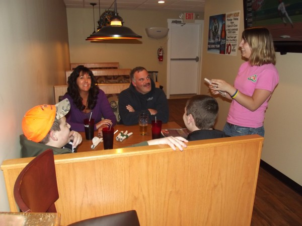 A waitress takes orders from a family of four at Pat's Pizza in Machias.