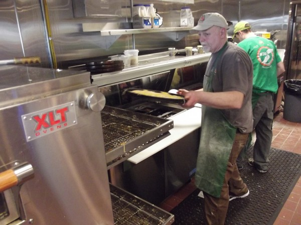 Bill Burke prepares to load a pizza into an oven at his Pat's Pizza franchise in Machias.
