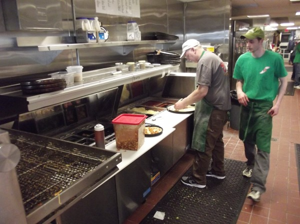 Bill Burke makes a pizza at his Pat's Pizza franchise in Machias as his son, 'Nate,' strides into the kitchen area.
