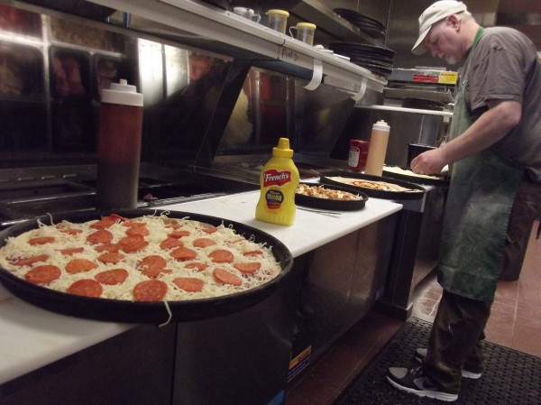 Bill Burke makes pizzas for customers at his Pat's Pizza franchise in Machias.