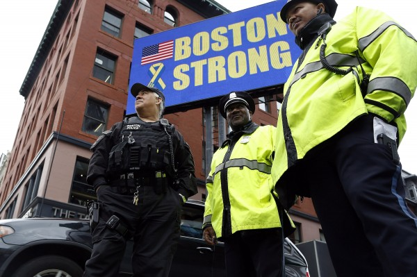 Boston police stand beneath a &quotBoston Strong&quot sign near the site of one of the two bomb blasts on the anniversary of the 2013 Boston Marathon bombings in Boston, Mass., on Tuesday.