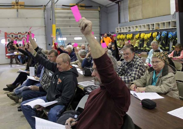 Residents approve an article by a show-of-hands vote at Sangerville''s annual town meeting on March 29.