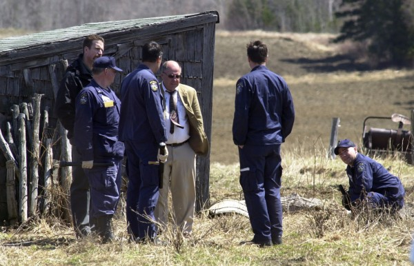 Maine State Police crime scene investigators congregate near a lean-to on Daniel Bondeson's property on May 4, 2003. Bondeson was found shot days before. Police have linked him to the arsenic poisonings in nearby New Sweden.